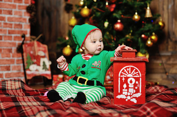 child dressed as an elf sitting on a plaid background on the Chr