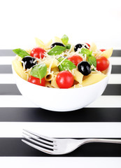 Pasta with tomatoes, olives and basil leaves in bowl