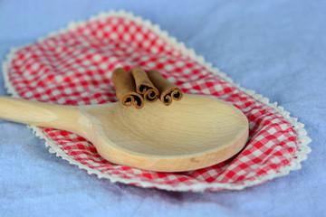 Kaneelstokjes gedecoreerd op houten pollepel en geruit kleedje,