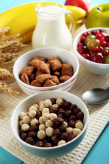 Various sweet cereals in ceramic bowls, fruits and jug with