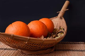 Fresh oranges fruits on wooden handmade plate on black