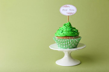 Delicious cupcake with inscription on green background