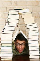 Mann schaut unter Bücherturm hervor