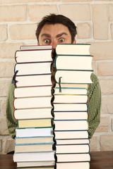 Mann schaut über, hinter Büchertapel hervor