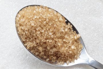 Brown sugar on spoon and white sugar in background
