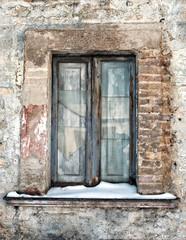 vecchia finestra con vetri rotti e neve sul davanzale