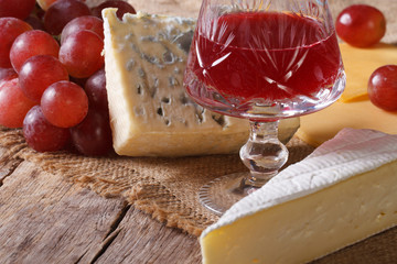 Red wine with cheese and grapes close-up horizontal