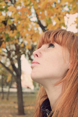 Dreamy red hair girl face with freckles against red autumn folia