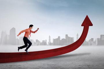 Businessman running on red arrow