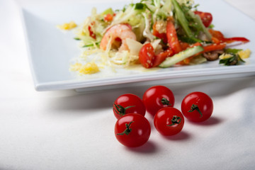 Fresh cherry tomatoes and salad with shrimps backwards