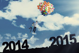 Couple flying with balloons above number 2014 to 2015