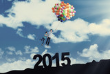 Couple with balloons above number 2015