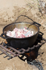 meat in a cauldron on fire