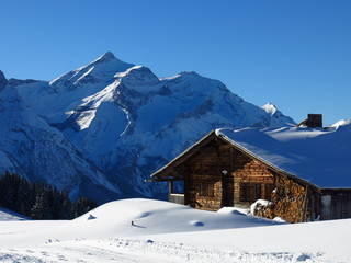 Snow covered Oldenhorn and facade of a farmhouse