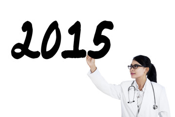 Female physician writes number 2015 on whiteboard