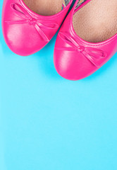 Part of pink shoes on blue background