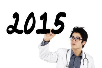 Male physician writes number 2015 on whiteboard
