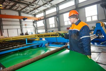 worker at metal sheet profiling factory