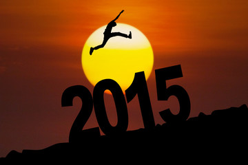 Silhouette of man jumps above number 2015