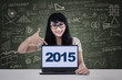 Student pointing numbers 2015 on laptop