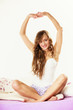 woman waking up in bed stretching her arms up