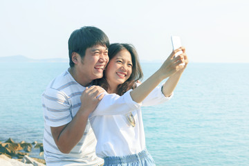 young man and woman take a photo by smart phone at sea side use