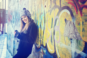 Smiling teenage girl with tablet outdoors against graffiti wall