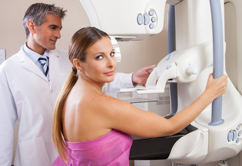 Woman undergoing mammography scan assisted by male doctor