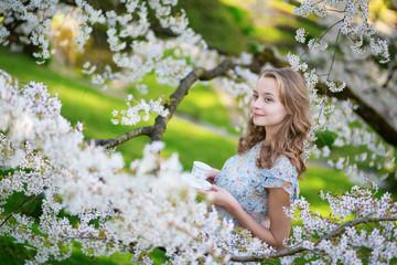 Girl drinking tea in cherry garden on a spring day