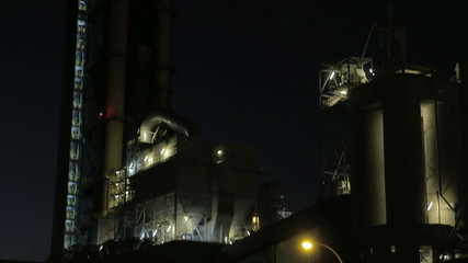 Establishing shot of a cement factory at night. Panning shot.