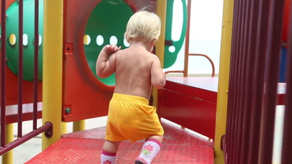 baby girl plays on the playground running and clapping