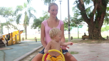 baby swings for the first time with mother on a swing in the par