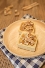 Fresh delicious caramel nut tart dessert on wood board