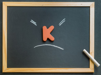 Wooden K character on black board