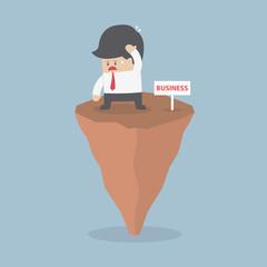 Businessman standing on unstable rock, Business risk concept