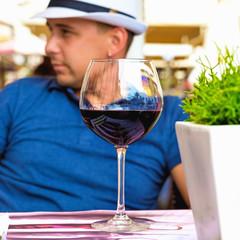 Портрет мужчины в кафе с бокалом красного вина.