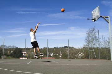 Basketball player taking a jump shot on an outdoor court