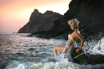 Beautiful young Sexy woman. Mermaid in the rocks on the beach.