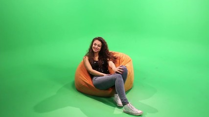 Girl smile on the green screen. sitting on bean bag