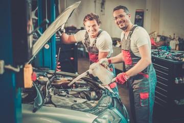 Two mechanics adding oil level in a car workshop