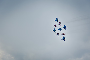 Aerobatics group of fighters on sky background