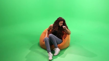 Girl relax on the bean bag. touch it and smile