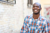 Black man wearing casual clothes in urban background poster