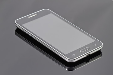new smartphone is lying on a black reflective surface