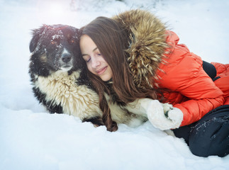Girl with a dog in the snow.