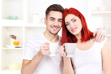 Happy couple drinking tea in kitchen
