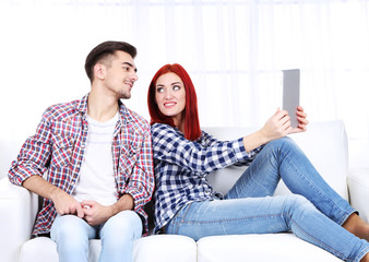 Young couple sitting in sofa with notebook in room
