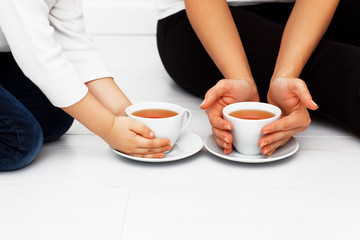 Mother with child warming hands with cup of tea