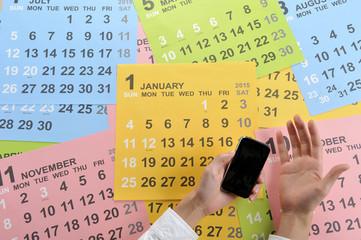 アナログのカレンダーとスマートフォンで予定を確認する様子