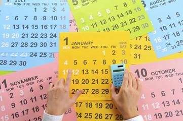 カレンダーと電卓を持っている人間の手
